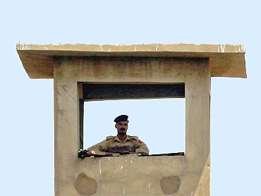 A soldier keeps guard from a watch tower around the compound walls of the Mehran naval aviation base in Karachi