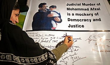 Tabassum Guru, wife of Afzal Guru, signs on a banner with her husband's and son's picture in Srinagar in 2006
