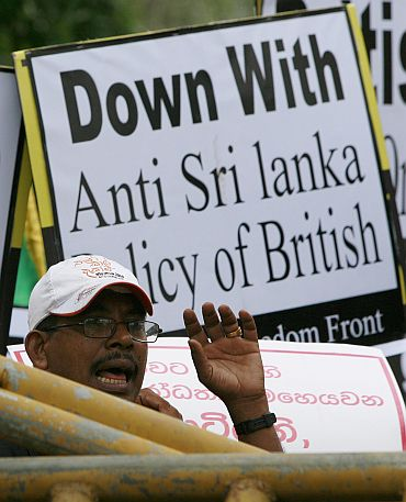 A pro-government supporter shouts behind police barriers outside the British High Commission in Colombo