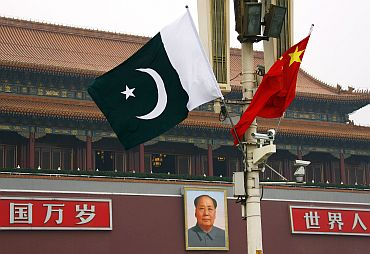 Pakistan flag flies alongside a Chinese flag in front of the portrait of Chairman Mao Zedong on Beijing's Tiananmen Square