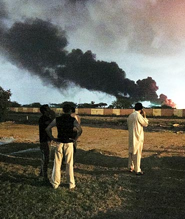 Men watch as a plume of smoke rises from the Mehran naval aviation base after it was attacked by militants in Karachi