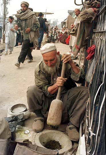 An elderly vendor grinds tobacco leaves to make traditional Naswaar, a mild stimulant, at a Peshawar market