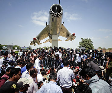 Media gather at the gates of the Mehran naval aviation base after troops ended operations against militants in Karachi