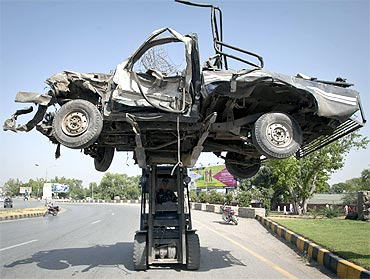 A damaged vehicle is cleared from a police station, which was destroyed by a car bomb, in Peshawar
