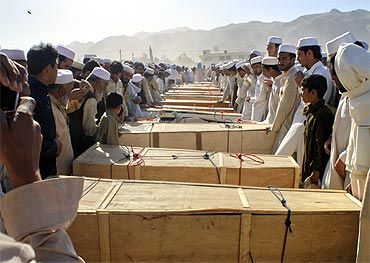 Residents stand over the caskets of those killed by a secondary blast at the site of a NATO tanker which was attacked in Pakistan's northwest Khyber Agency