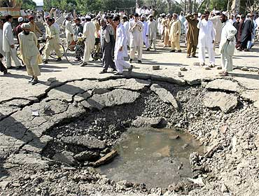 Residents gather next to a crater caused by a suicide bomb attack in the northwestern town of Hangu