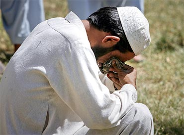 A man weeps at the burial site of a family member who died in a suicide bomb attack in the northwestern town of Hangu