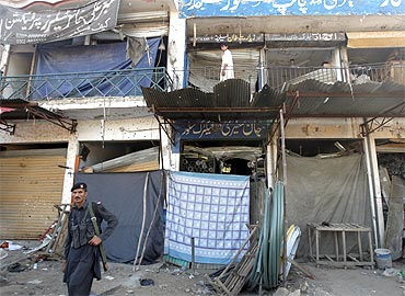 A soldier stands guard as a man collects his belongings from his destroyed shop in a market near the paramilitary academy, which was attacked by a suicide bomber in Charsadda, northwest Pakistan