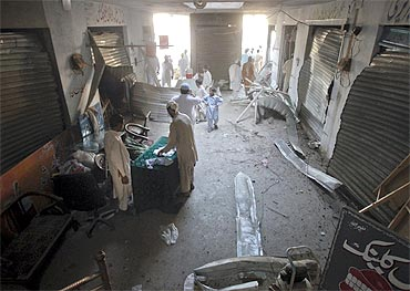 Men collect belongings from their damaged shops in a market near the entrance of a paramilitary academy, which was attacked by a suicide bomber, in Charsadda, northwest Pakistan