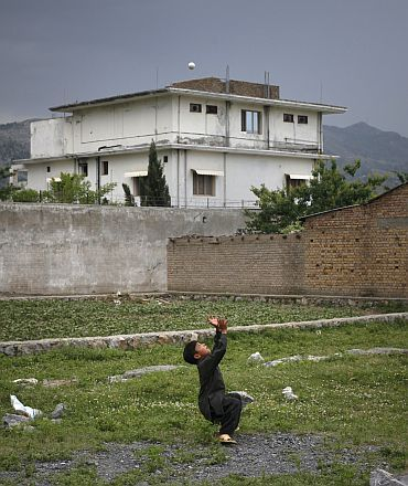 A boy plays with a tennis ball in front of the compound where US Navy SEAL commandos killed Osama bin Laden in Abbottabad