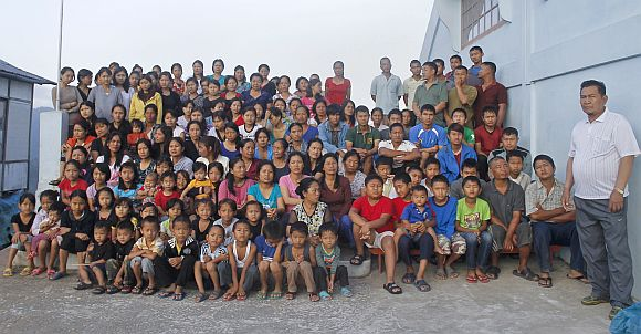 Family members of Ziona (Right) pose for a group photograph outside their residence in Baktawng village in Mizoram