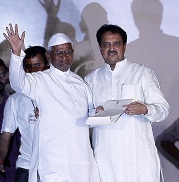 Hazare waves to his supporters after receiving a letter from PM Singh by Union Minister Deshmukh at Ramlila grounds in New Delhi