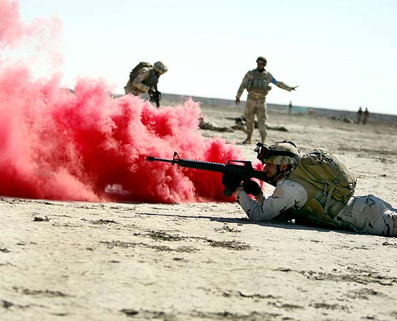 Coloured smoke is seen as an Iraqi soldier fires at targets during a training course supervised by the US Army at a military base in Nassiriya