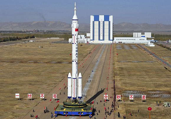 Employees transfer the Long March II-F rocket to the launchpad in the Jiuquan Satellite Launch Center