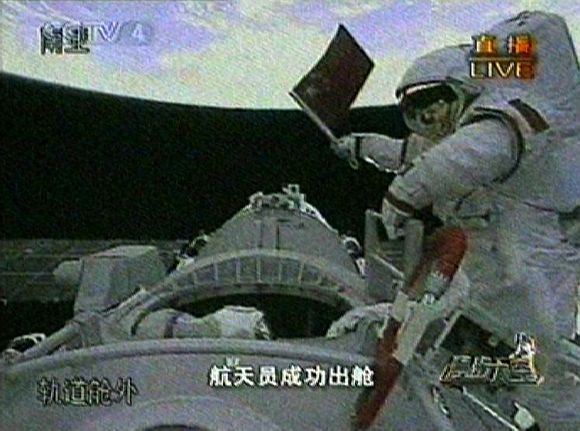 Video grab of astronaut Zhai Zhigang of China waving the national flag after exiting the Shenzhou VII space craft