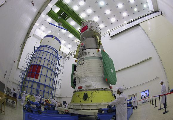 Technicians prepare to assemble the cover of the Shenzhou-7 manned spacecraft at the Jiuquan Satellite Launch Center