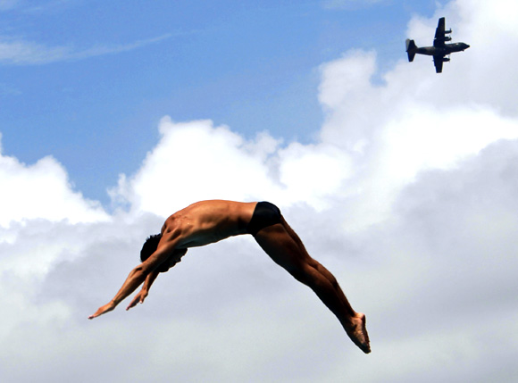 Mexico's Ivan Garcia dives as a C-130 Hercules transport aircraft flies past