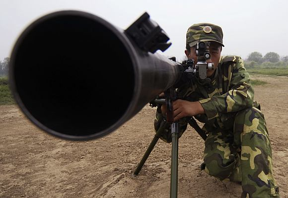 A soldier practices shooting during a training session at a military base in north China