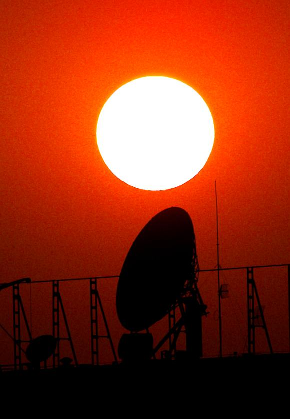 A satellite dish is silhouetted by the setting sun in Beijing.