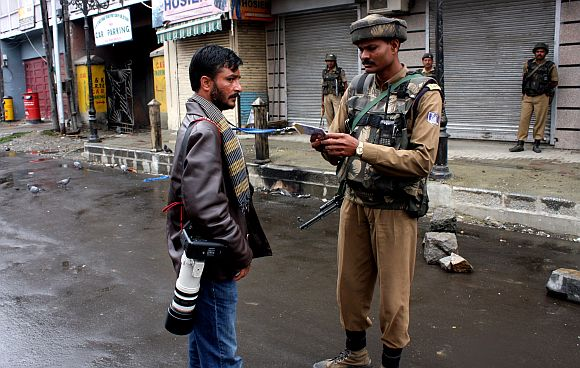 A soldier check the credentials of a photographer in Srinagar