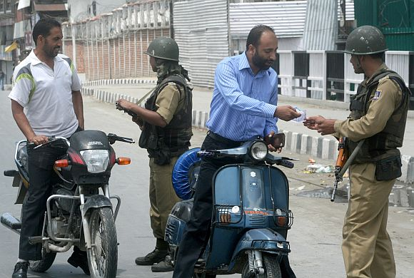 Paramilitary personnel frisking scooterists in Srinagar