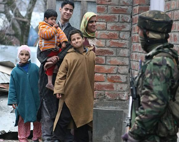 A Kashmiri family smiles at an army trooper