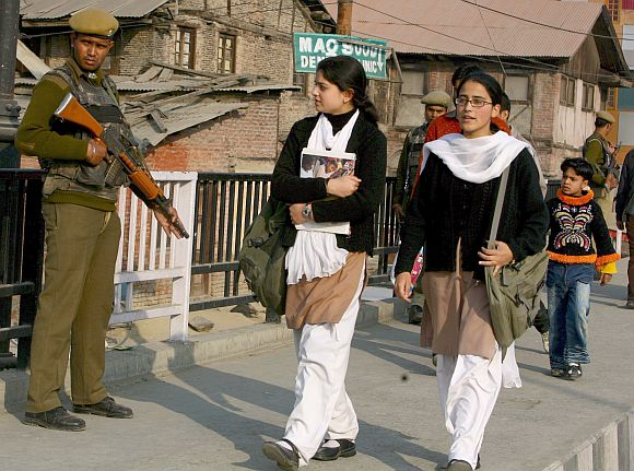 Schoolgirls walk past a paramilitary trooper in Jammu