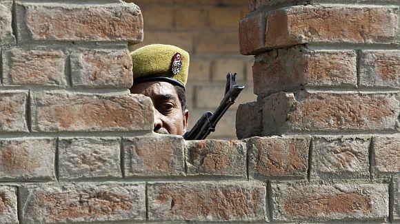An trooper keeps guard from a bunker after a grenade blast in a market in Srinagar