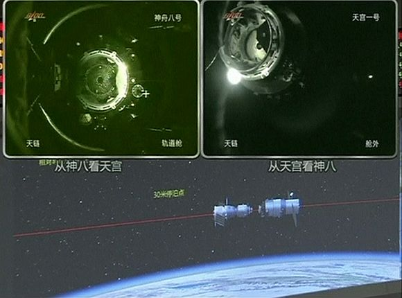 A view of China's Tiangong (Heavenly Palace) 1 module (top L) just before it docks with the Shenzhou 8 spacecraft (top R) is seen on a monitoring screen showing a computer animation (bottom) of the docking process at the Beijing Aerospace Flight Control Centre November 3