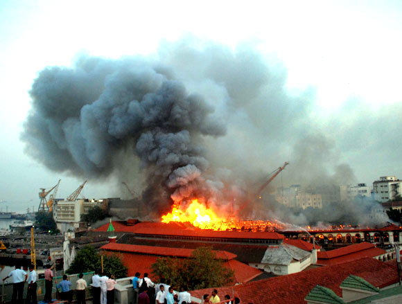 People watch a burning South Mumbai building from rooftops