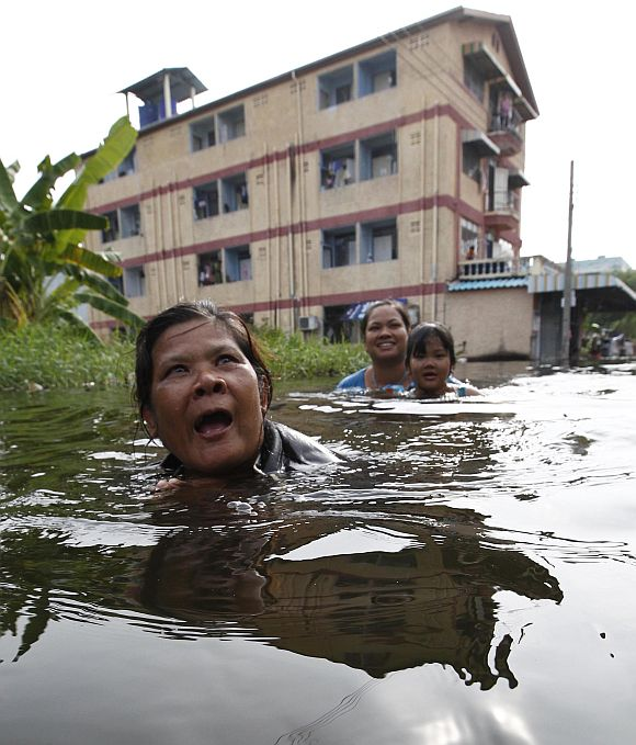 Residents walk through a flooded street in Bangkok on Sunday