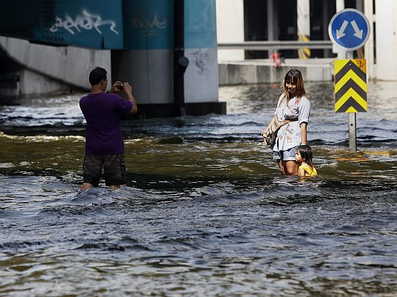 A resident uses his mobile phone to take a picture of his family at a flooded street in Bangkok
