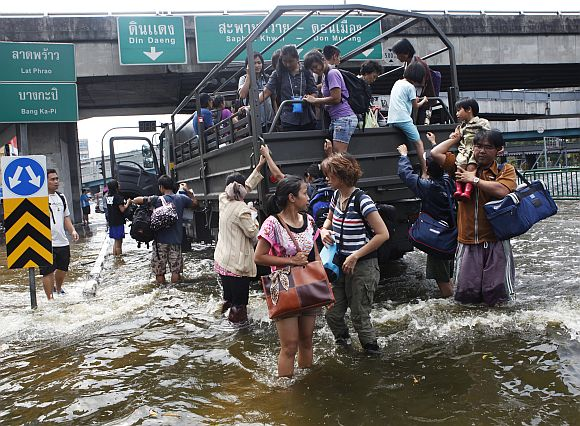 Residents disembark from a military truck as they are evacuated from a flooded area in Bangkok
