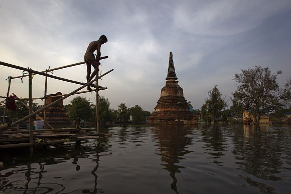 A resident builds a temporary shelter to escape flood waters near Wat Hasadawat temple in Thailand's ancient capital Ayutthaya.