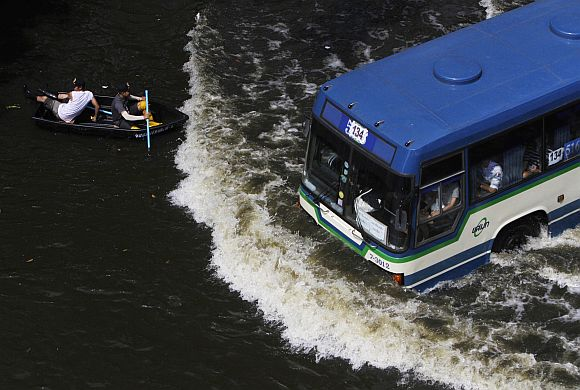 Residents travel on a boat as a bus drives on a flooded street in Bangkok