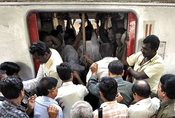 Commuters try to get in through an open doorway of a suburban train during the morning rush hour in Mumbai