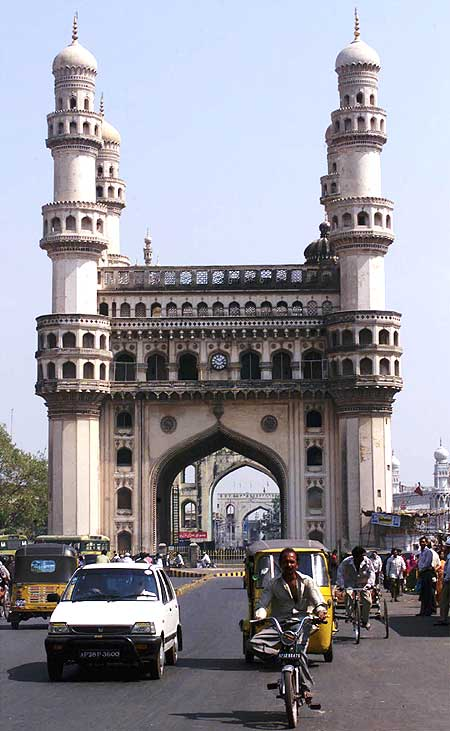 Residents of Hyderabad drive past the 'Charminar', the city's best known monument