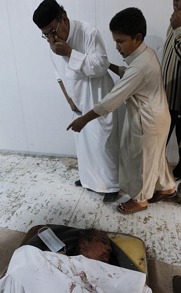 Libyan people visit the body of slain Libyan leader Muammar Gaddafi inside a storage freezer in Misrata
