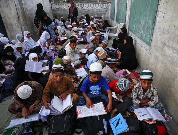 Students attend a rooftop evening class in a private school at a slum area in Karachi