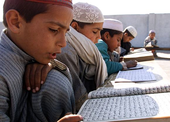 Young Pakistani Muslim students recite verses from the holy Koran at a Madrassa outside the Pakistan capital Islamabad