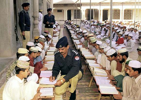 A Pakistan police officer registers student at a religious school in Punjab provincial city of Multan