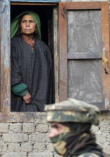 A file picture of a Kashmiri woman looking out of the window of her house as an army jawan guards during a gunbattle with militants near Srinagar