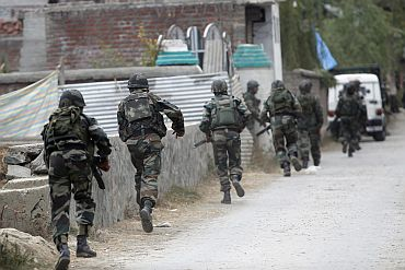 Army soldiers run towards the site of gunbattle with suspected militants in Maloora on the outskirts of Srinagar