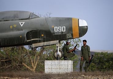 Military personnel keep guard under an old aircraft displayed at the Mehran naval aviation base after troops ended operations against militants in Karachi
