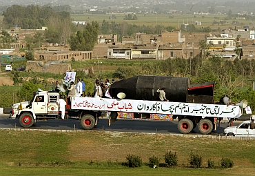 Members of the fundamentalist youth organization, Shabab-e-Milli, drive a truck carrying a mock nuclear bomb through Islamabad, as part of its campaign to build support for Pakistan's nuclear programme