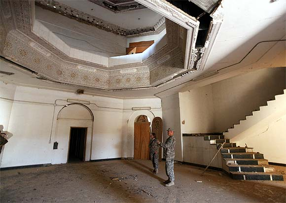US soldiers tour a building within Victory Base Compound in Baghdad on November 7. The US military is vacating Saddam Hussein's ornate palaces at its war headquarters in Baghdad and will turn the property over to Iraq next month, but Saddam's prison toilet is leaving with the Americans.