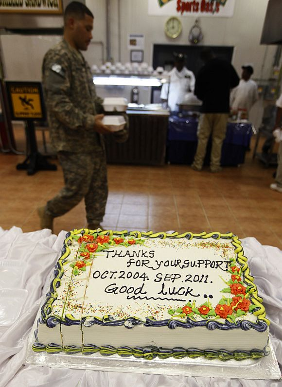 A US soldier walks past a cake at Camp Liberty in Baghdad