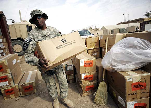A US soldier carries boxes to be shipped out of Iraq during preparations ahead of a pull-out at Base Kalsu, south of Baghdad