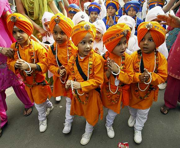 Sikh boys dressed as Panj Pyaare, or the five beloved of Sikh Gurus, take part in a procession on the eve of the birth anniversary of Guru Nanak Dev, in Amritsar