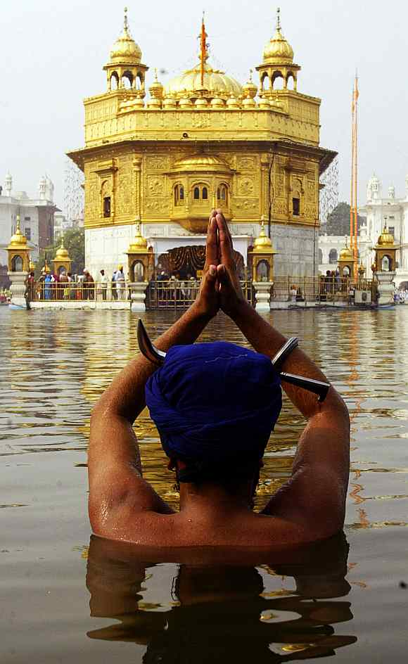 A Sikh devotee takes a dip in the pond at the Golden temple on the birth anniversary of Guru Nanak Dev in Amritsar